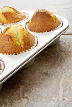 muffins made with lemons and poppy seeds. Hot out of the oven. Ceramic tile background. Stock Photo