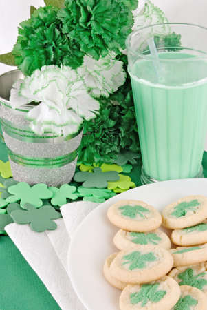 St. Patricks Day sugar shamrock cookies served with green milk. The background is decorated with green and white artificial flowers and the table is sprinkled with foam clovers.