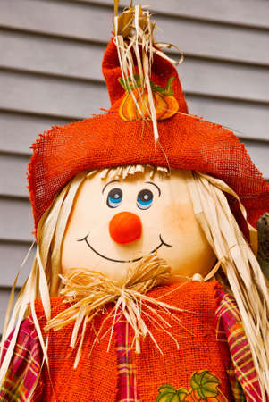 scarecrow wearing bright orange clothes and a big smile on his face.