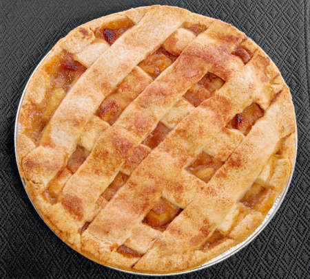 apple pie served on a black place mat.  photo