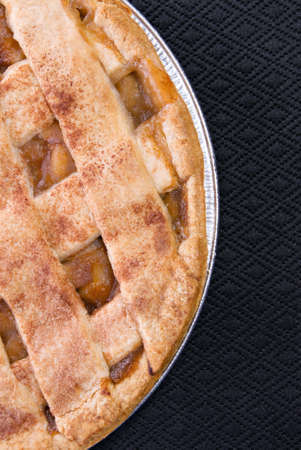 apple pie served in a tin pan on a black place mat.