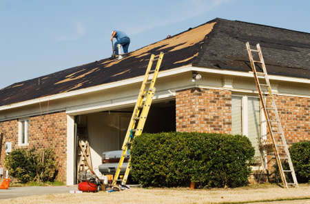 Roofer repairing the roof of a brick house in the suburbs