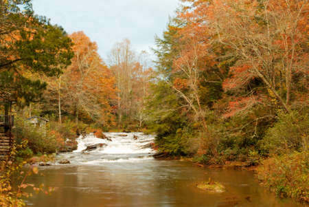 Soque River in Clarkesville Georgia USA during the autumn season. A small waterfall is the focus of this image.  photo