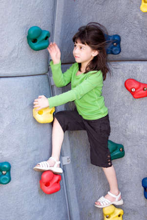 girl climbing a fake rock wall. She is six year old.  Stock Photo