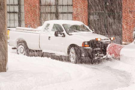 ploegen: vrachtwagen met sneeuwschuiver gehecht werken de straat tijdens een sneeuwstorm.