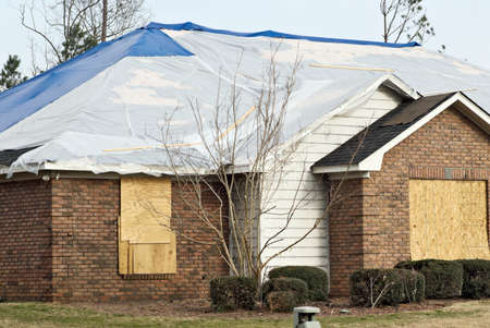 tornado damaged house with boarded windows and plastic tarps on the destroyed roof  Debris is stuck to the house