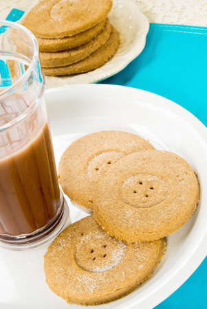 Light chocolate cookies served with a glass of chocolate milk.