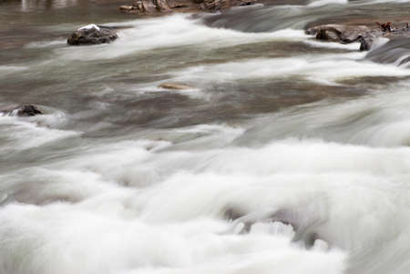 Flowing water with snow-capped rocks. Natural color. Slow shutter speed created silky smooth look.