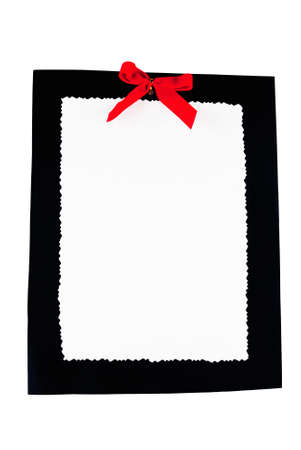 blank white paper with a scalloped edge on top of a piece of black cardboard with a red ribbon. Isolated White Background. Stock Photo