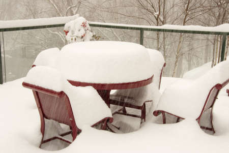 Snow covering outdoor furniture during a blizzard. Shot outdoors during the storm.