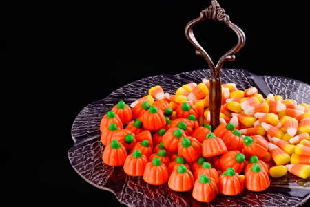 Halloween candy served in an antique serving dish. Black background.