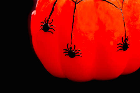 Halloween decoration. Illuminated wax pumpkin with dangling wax spiders. Copy Space. Black background. photo