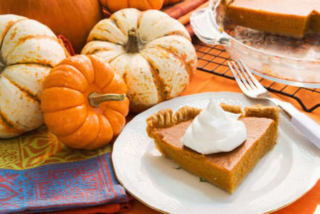 Slice of pumpkin pie served on antique china. Bacground of assorted pumpkins and what is left of the baked pie. Stock Photo