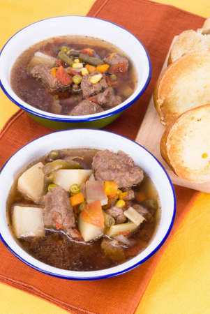Homemade beef soup served with buttered toasted crusty italian bread. Soup ingredients are potatoes, mixed vegetables, low sodium beef broth, onions, celery, garlic and various herbs and spices. Shallow definition of field. Stock Photo