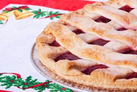 Cherry pie on a Christmas placemat. Homemade pie is served in a tin pie pan. Copy space.