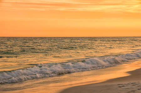 destin: Sunset at Destin Beach Florida USA in warm brilliant colors of orange, yellow, brown and green. This image was shot with a long exposure causing the wave in the front of the image to have a silky smoth appearance. This gorgeous relaxing at the waters edge