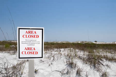 outdoor sign protecting the white sand dunes and sea oats at Camp Helen State Park in Panama City Beach Florida along the Gulf of Mexico. The sign states the area is closed and is a protected environmentally sensitive area and cannot be disturbed by human photo