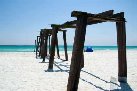 tent city: Camp Helen State Park pier in Panama City Beach Florida. There is a beach tent set up in the white sand with fishing poles stuck in the beach for surf fishing. The Emerald Coast is a sought after travel location in the southern United States.