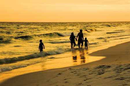 destin: A family of four walking along a beach in Florida during sunset on a warm summer night. The mom and dad and one child are walking along hand in hand. The older child is standing in the gentle waves admiring the colors and the waters along the Emerald Coas Stock Photo