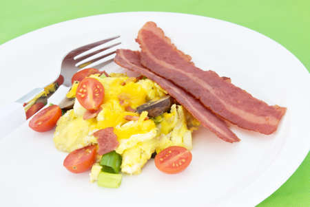 Scrambled egg served with two sliced of fried turkey bacon. Eggs are made with small sliced grape tomatoes sliced bella mushrooms green spring onion and cheddar cheese. There is a clean new fork on a white plate. The background is a lime green place mat. Stock Photo