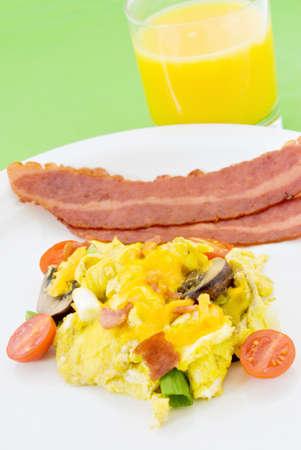 turkey bacon: Uova strapazzate servite con due fette di pancetta fritta tacchino con un bicchiere di succo d'arancia. Le uova sono realizzati con funghi bella pomodorini uva affettata verde cipollotto e formaggio cheddar. Lo sfondo � una calce tappeto verde del luogo.