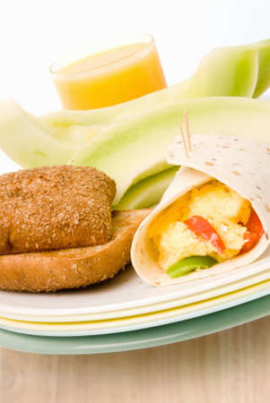 multi grain sandwich: Homemade scrambled egg breakfast burrito served in a wrapped flour tortilla held together with two toothpicks. Sliced fresh honeydew melon and a glass of orange juice are on the back side of the stacked plastic plates. Ciabatta multi grain brown bread rol Stock Photo