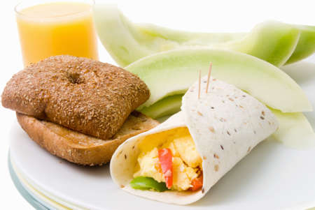 Homemade scrambled egg breakfast burrito served in a wrapped flour tortilla held together with two toothpicks. Sliced fresh honeydew melon and a glass of orange juice are on the back side of the stacked plastic plates. Ciabatta multi grain brown bread rol Stock Photo