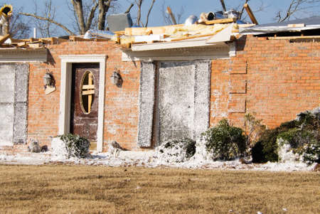 dormant: Tornado destroyed brick house with white insulation debris on the exterior surface as well as in the yard. The roof has been ripped off and the house has been boarded up. The lawn is dormant due to the time of year the EF2 tornado came through. Selective  Stock Photo
