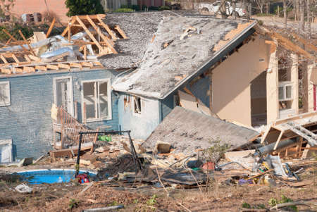 Aftermath of a tornado damaged blue wood framed house. The storm came through this residential neighborhood in March and damaged numerous houses in its path. Stock Photo