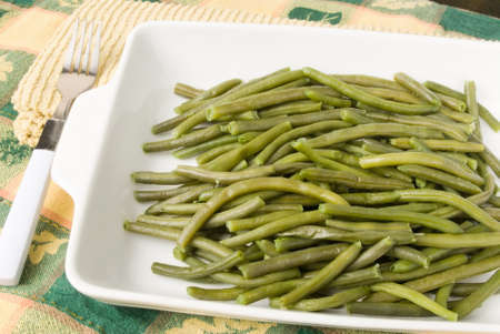 greenbeans: homemade cooked string green beans served in a white casserole dish. There is a fork lying to the side on a stack of yellow kitchen napkins. The background is a Thanksgiving themed tablecloth.