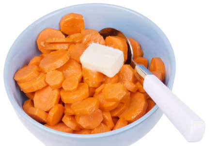 Cooked sliced orange organic carrots topped off with a dollop of butter and served in a blue bowl. There is a spoon inside the bowl and the background is white.