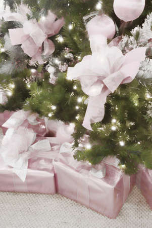 coordinated: Christmas presents wrapped in pink paper with color coordinated matching ribbons and christmas tree decorations. This is computer generated art from a photograph. Stock Photo