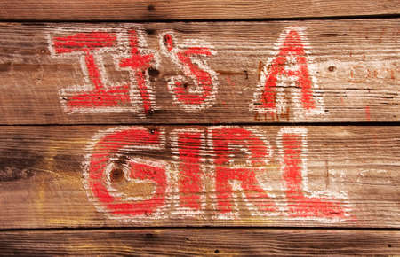 it's: its a Girl birth announcement painted with red paint with a white border around the letters. The background is an old wooden wall on the exterior of a building.