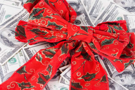 red bills: A bright red Christmas bow on top of a bed of stacked US 100 one hundred dollar bills. Stock Photo