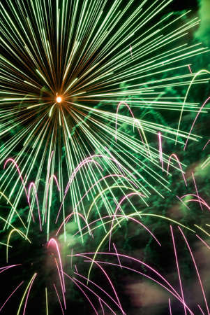 firework display: Exploding firework display in the colors of green and pink. Stock Photo
