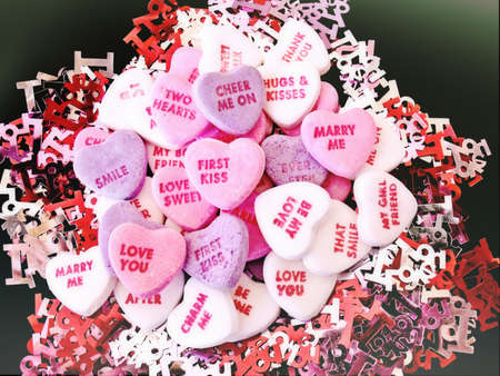 short phrase: Valentines Day candy conversation hearts with various short phrases on a bed of I Love You confetti. Stock Photo