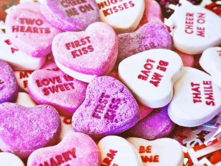 short phrase: Valentines Day candy conversation hearts with a film grain textured effect.