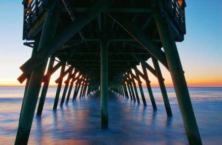 peaceful: Sunrise at Myrtle Beach State Park pier in South Carolina. A long exposure creates a peacful scene under the pier.