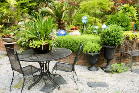 garden furniture: Wrought iron outdoor patio furniture in a landscaped flower garden. Stock Photo