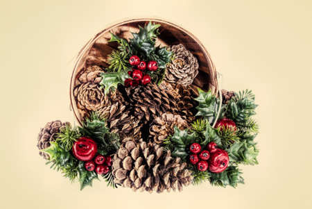 Winter christmas holiday wooden basket filled with pine cones and holly leaves with berries. This is computer generated art from a photograph. Stock Photo