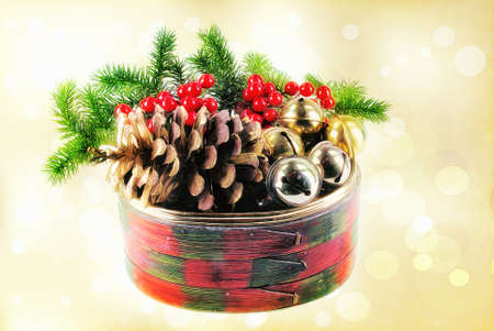 pinecone: Christmas winter holiday decorations with a textured effect. The colorful wooden basket is filled with pine cones, greenery, bells, and berries. This is computer generated art from a photograph. Stock Photo