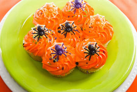 homemade halloween cupcakes decorated with toy plastic spiders  served on a lime green plate with an orange colored background. Stock Photo