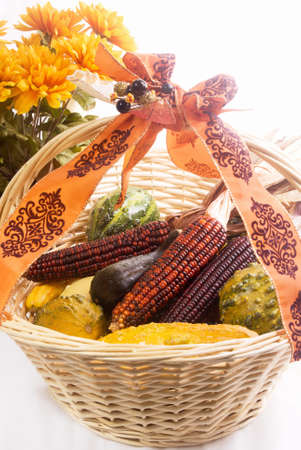 Autumn gourds and indian corn in a wooden basket with chrysanthemum flowers in the background.