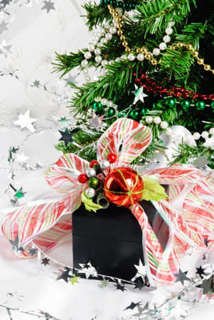 Wrapped black Christmas present with a red and white striped ribbon tied in a bow. The holiday present is surrounded with strands of pearls and star shaped silver garland.