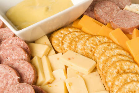 Assorted meat and cheese delicatessan holiday platter. Served with yellow mustard in a white ceramic bowl and crackers.
