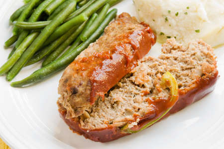 Homemade meat loaf served with mashed potatoes and fresh green beans.