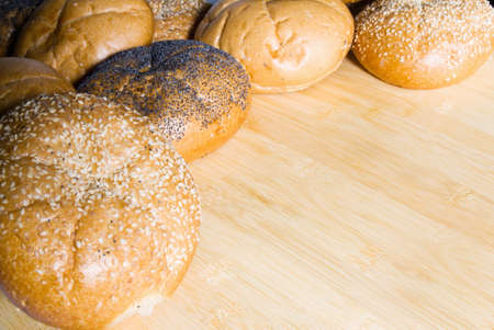 An assortment of bread rolls served on a wooden cutting board with copy space. Stock Photo