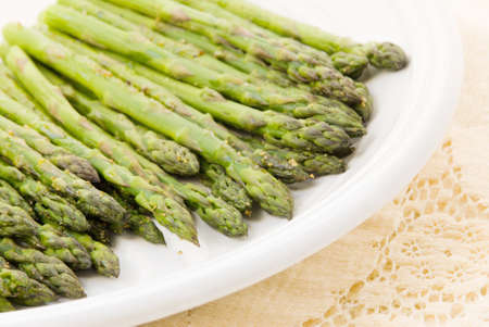 Homemade roasted asparagus covered with various herbs and served on a white plate. The background is an old antique tablecloth. Selective focus with shallow definition of field.
