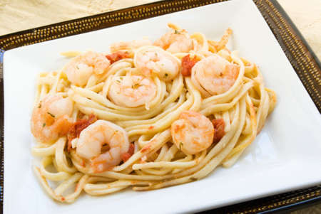 Homemade shrimp scampi served on a bed of linguini pasta noodles served on double square plates and an antique tablecloth in the background. Stock Photo