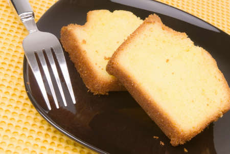 Cut slices of homemade lemon cake served on a black colored glass plate with a stainless steel fork.